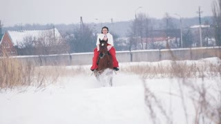 Young brunette in a red dress galloping fast on a horse through the snow-covered field in the winter