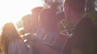 Young caucasian friends having fun and singing songs with a guitar in summer park at sunset