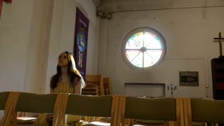 Young caucasian religious devoted woman on the bench in Catholic Church