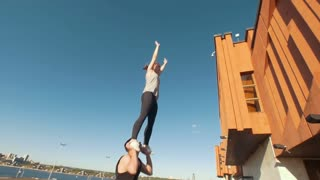 Young cheerleaders workout outdoors at cityscape on background - young man holding the girl performing flip in the air