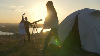 Young couple calling their friend to looking through telescope at sunset on the hill