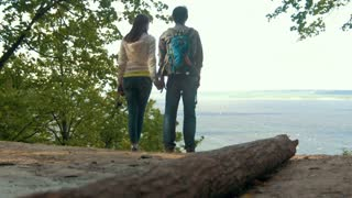 Young couple in love standing on high hill, looking to river