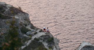 Young couple sitting on rocky cliff by the sea
