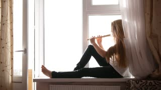 Young cute teen girl playing on flute sitting on windowsill at home