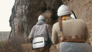 Young explorers in helmets enters to the large dark cave with flashlights