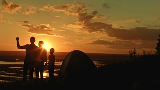 Young family - father, mom and son in camping - stands on high hill at summer sunset and have happy, silhouette