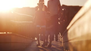 Young family walking on the bridge against the beautiful sunset. The children run ahead. Parents following behind, holding hands.