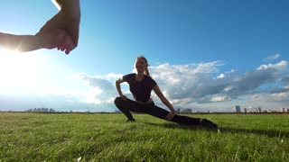 Young female acrobat workout on the grass at summer sunset