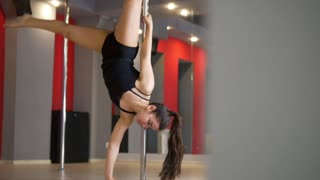 Young flexible woman performing handstand with a pole in a studio