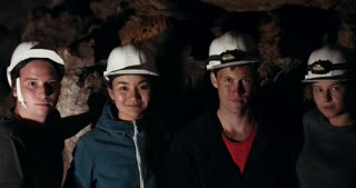 Young friends explorers looking at camera in a dark cave