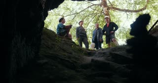 Young friends in helmets sitting in front of the dark cave in forest
