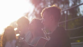 Young friends singing songs with a guitar in the park at sunset