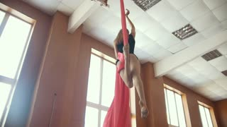 Young girl acrobat shows flexibility on gymnastic cloth, slow-motion