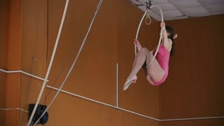 Young girl acrobats with a gymnastic hoop on the height