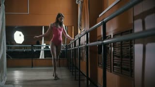 Young girl performs flexibility of the body at the ballet bar, slow-motion