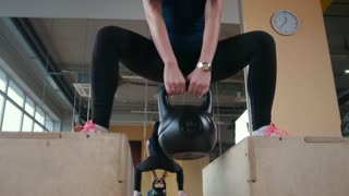 Young girl working out doing squats with weigh in the gym, bottom view