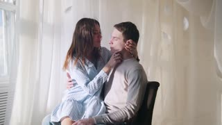 Young guy and girl sitting by the window in a brightly lit room, hugging and kissing