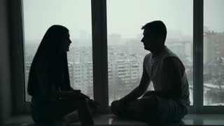 Young happy couple sitting on the windowsill, emotionally talking, arguing and gesticulating