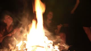 Young happy friends sing songs around the campfire at night