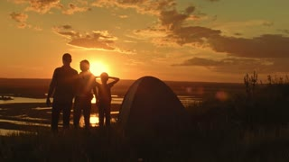 Young happy healthy family - father, mom and son in camping - stands on high hill at summer sunset and have happy, silhouette