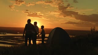 Young happy healthy family - father, mom and son in camping - stands on high hill at summer sunset and looking to horizont