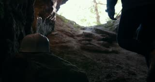 Young hikers in helmets climbing up from the dark cave