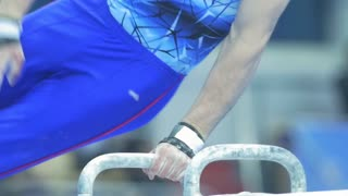 Young male gymnast whirling on the pommel horse