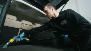 Young man cleans the car interior with vacuum cleaner