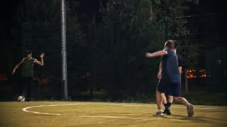 Young man kicks a ball that flies past other football players and past the gate, night shooting football game