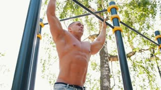 Young man performs a power exercise on horizontal bar