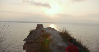 Young man standing on the edge of a cliff and meets the sun