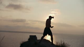 Young man warming up on a top of a cliff at sunrise