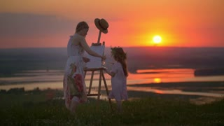 Young mother and little daughter drawing landscape together on the hill at sunset