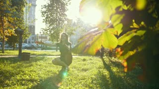 Young mother plays with little son in summer park at sunset - slow-motion