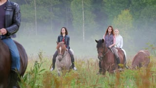 Young people riding horses in nature early in the morning
