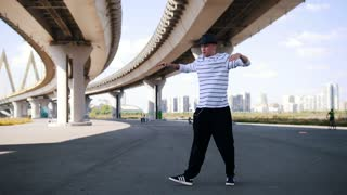 Young popper in hat and striped t-shirt dancing under the bridge in summer