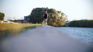 Young Sports Woman Running Near River