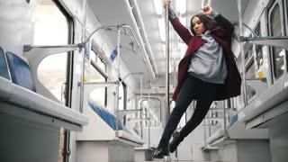 Young woman dancing in subway train
