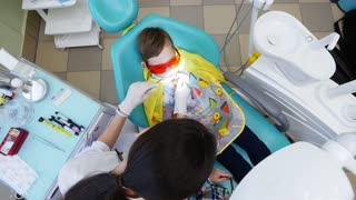 Young woman dentist treats a little boy's teeth, the brother of the boy-patient sits next to him