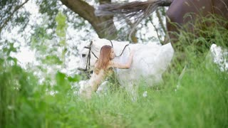 Young woman in swimsuit stroking a white horse outdoors