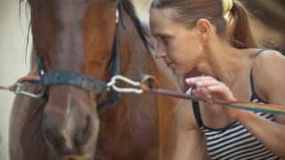 Young woman releases the horse. Close up shot