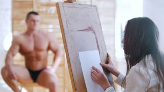 Young woman sits behind handsome male shirtless model and drawing him