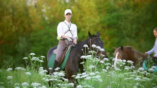 Young women ride on horseback through the field at sunset