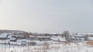 View of typical Russian village at winter - cold day in snow-covered field