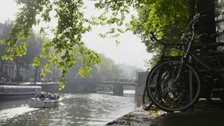 View of wheel of bicycle on the Amsterdam amstel canal, next to floats tour boat, sunny european autumn