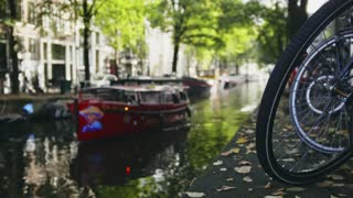 View of wheel of bicycle on the Amsterdam canal, next to floats tour boat, sunny european autumn