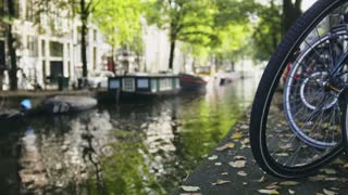 View of wheel of bicycle on the Amsterdam canal, sunny day