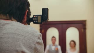 Wedding photographer takes pictures of newlyweds
