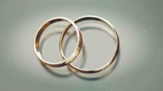 wedding rings lie on a grey background, glare from light