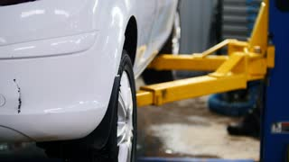 White car on lifts for repairing, automobile service